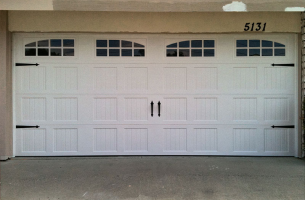 steel carriage house with decorative hardware garage door